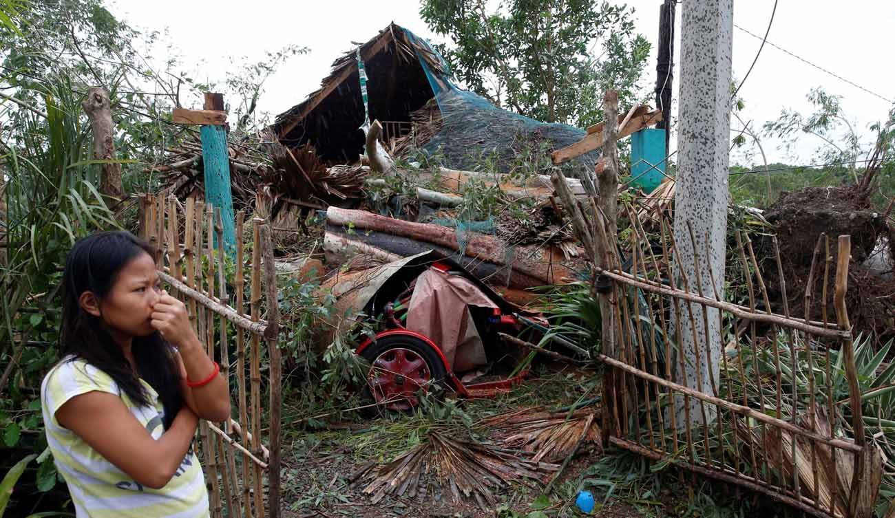 A woman in Bangui, Philippines, stands outside her house damaged by a fallen tree Oct. 20 after Typhoon Haima hit. Heavy damage was reported to homes and farmland in the northern Philippines after the strongest storm in three years struck overnight. (CNS photo/Erik De Castro, Reuters)