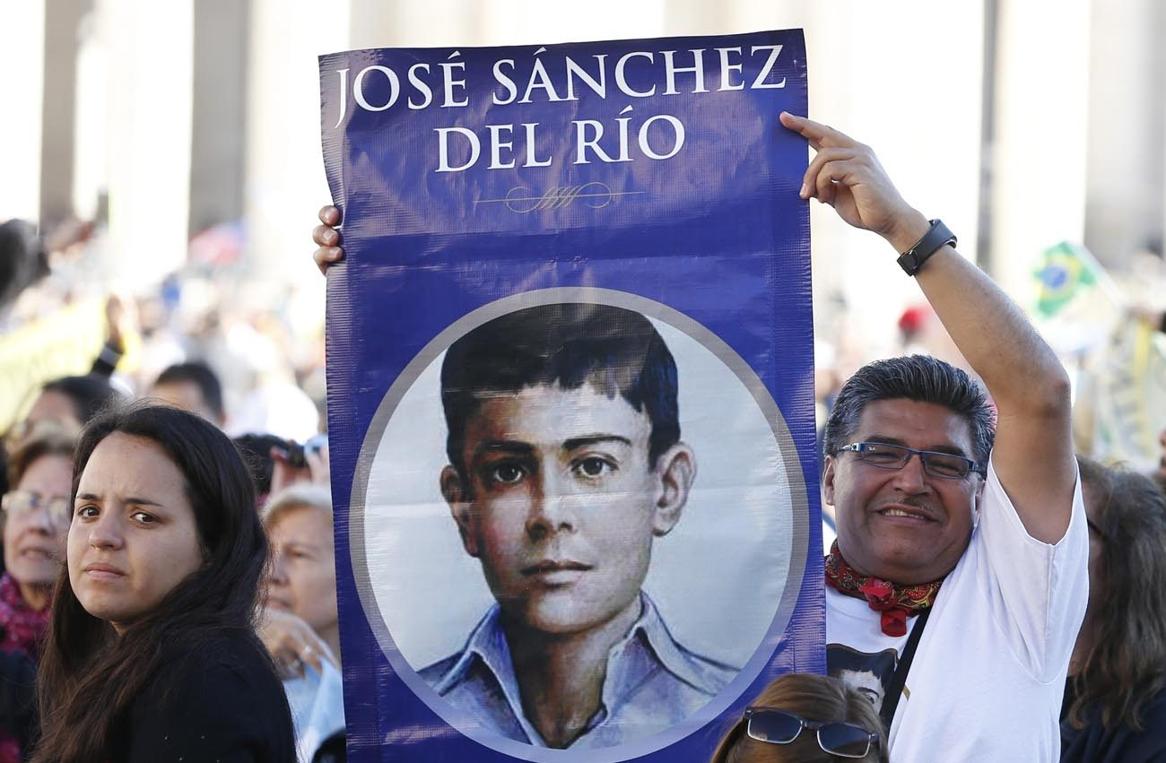 A man holds an image of new Mexican St. Jose Sanchez del Rio, who was martyred at the age of 14 in 1928, before the canonization Mass for seven new saints celebrated by Pope Francis in St. Peter's Square at the Vatican Oct. 16. (CNS photo/Paul Haring)