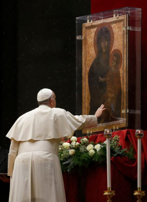 "Pope Francis touches the Marian icon ""Salus Populi Romani,"" (health of the Roman people), during a Marian vigil in St. Peter's Square at the Vatican Oct. 8. (CNS photo/Paul Haring)"