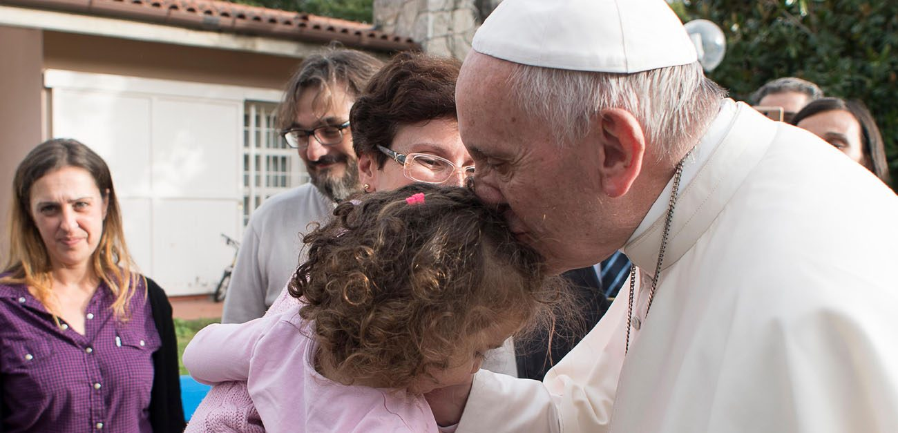 Pope Francis kisses a girl during an Oct. 14 visit to Rome's SOS Children's Village. (CNS photo/L'Osservatore Romano)