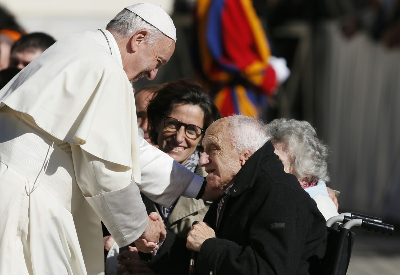 Pope Francis greets a man in a wheelchair during his general audience in St. Peter's Square at the Vatican Oct. 12. The pope called for an immediate cease-fire in Syria so that civilians can be rescued. (CNS photo/Paul Haring) .