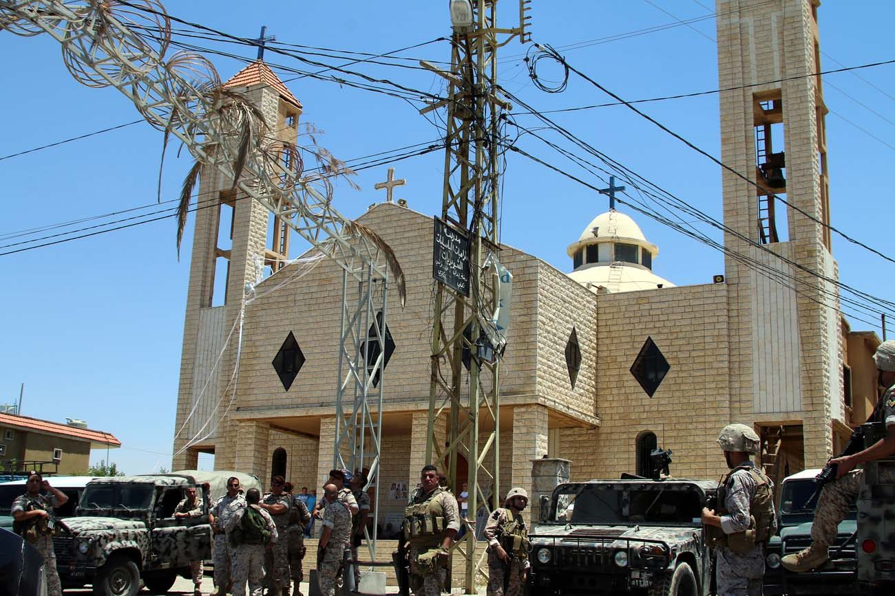 Lebanese army soldiers stand on an armored truck next to a church during a patrol after bombings in late June in Qaa. When a series of bombs exploded in the Lebanese Christian village near the Syrian border, it not only changed the lives of the victims and their families, but also the lives of Syrian refugees living nearby. (CNS photo/EPA)