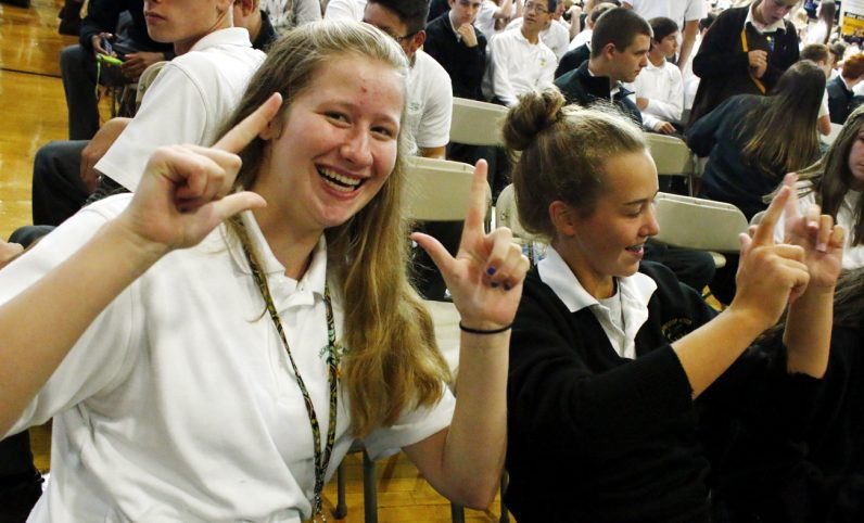 "Katie Leinenbach and Grace Fanning from Archbishop Wood say ""Yes Lord"" in sign language."