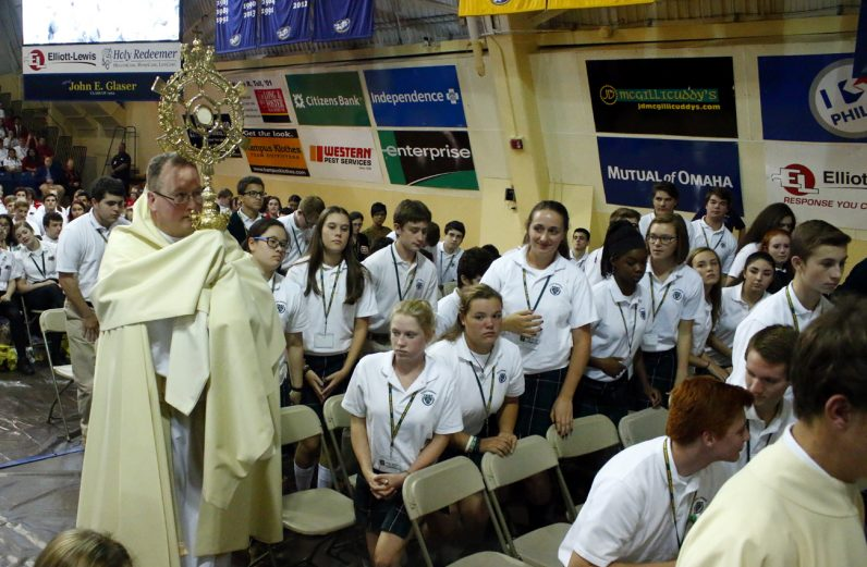Father Stephen DeLacy carries the Blessed Sacrament in procession during the youth rally in Tom Gola Arena at La Salle University.