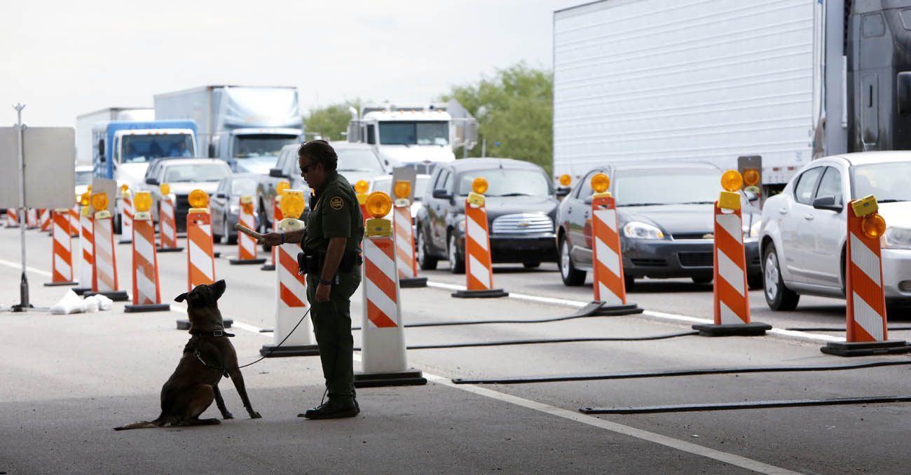 An agent handles a canine as vehicles wait to pass a Border Patrol checkpoint along I-19 north of Nogales, Arizona, July 16, 2014. The Catholic-founded SOA Watch human rights group planned to bring its annual demonstration to the border area Oct. 7-10. (CNS photo/Nancy Wiechec)