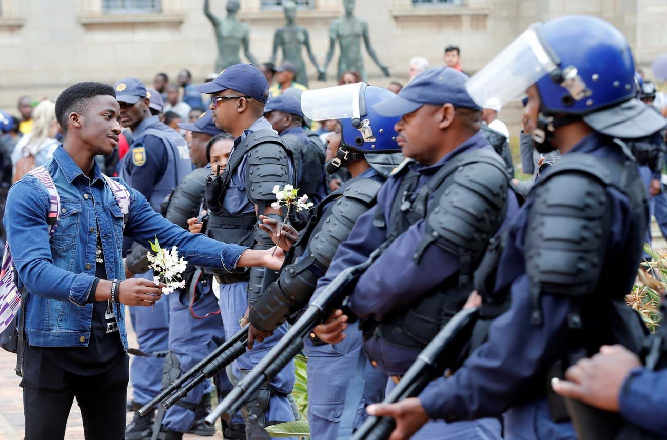 A student offers a flower to a police officer after clashes over high tuition fees Oct. 4 at the University of the Witwatersrand in Johannesburg. As students and police clash at South African universities, with many campuses closed because of protests against fee increases, Catholic students called on the government to increase its education budget. (CNS photo/Siphiwe Sibeko, Reuters)