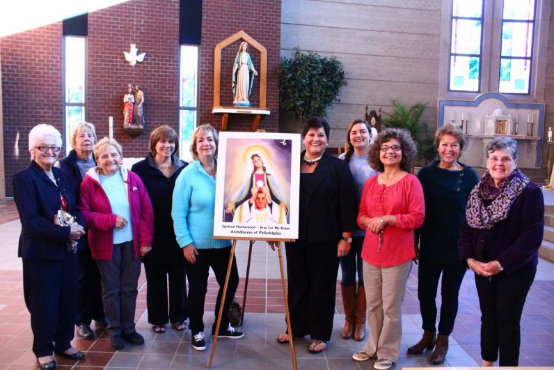 "Standing around a poster of the prayer program for priests are the ""spiritual mothers"" at St. Maria Goretti Church in Hatfield. They include Catholic radio host Kathleen McCarthy center left) and program founder Maria Carmel Richardson Center right)."