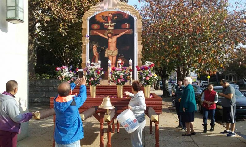 Parishioners decorate the platform with flowers prior to the procession outside St. William Church, which gave people attending earlier Masses at the church a chance to see the image and meet some of the devotees. (Gina Christian)