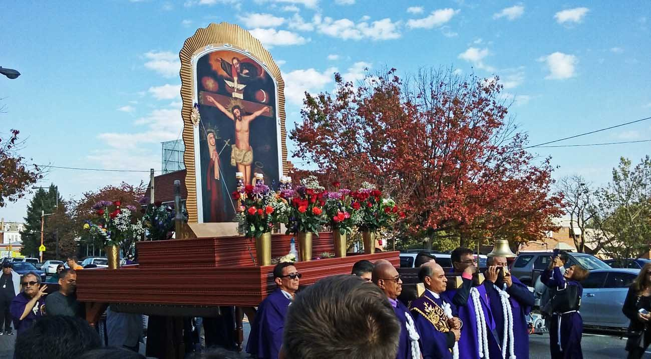 "Men of the Peruvian community at St. William Parish in Philadelphia take turns carrying a heavy wooden platform to display an image of El Señor de los Milagros (""The Lord of the Miracles"") on the streets of Lawncrest in Northeast Philadelphia during the annual devotion. (Photo by Gina Christian)"