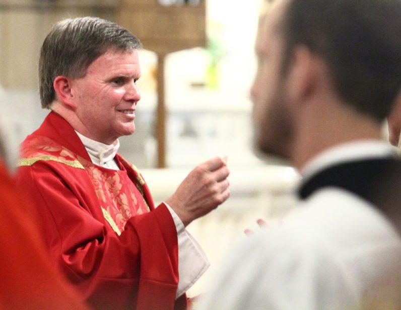Father Thomas Heron, St. Matthew's pastor, distributes holy Communion.