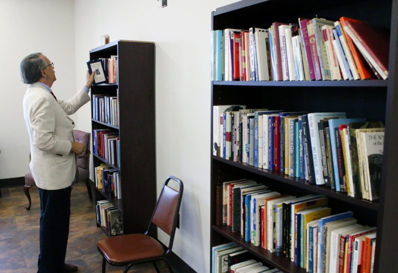 Stephen Aspero, a long-time friend of Mary Ann Lewis, checks out a book in the new room named for her.