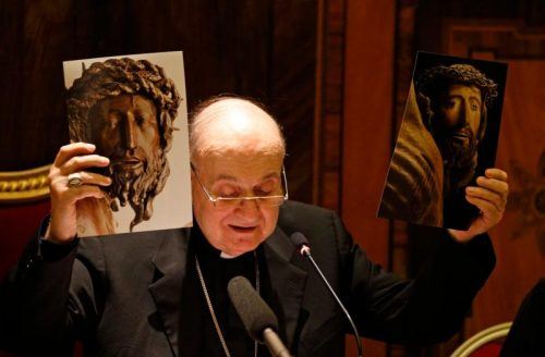 Cardinal Angelo Comastri, archpriest of St. Peter's Basilica, holds before and after restoration photos of a wooden crucifix from the 14th century during a media opportunity in St. Peter's Basilica at the Vatican Oct. 28.  (CNS photo/Paul Haring)