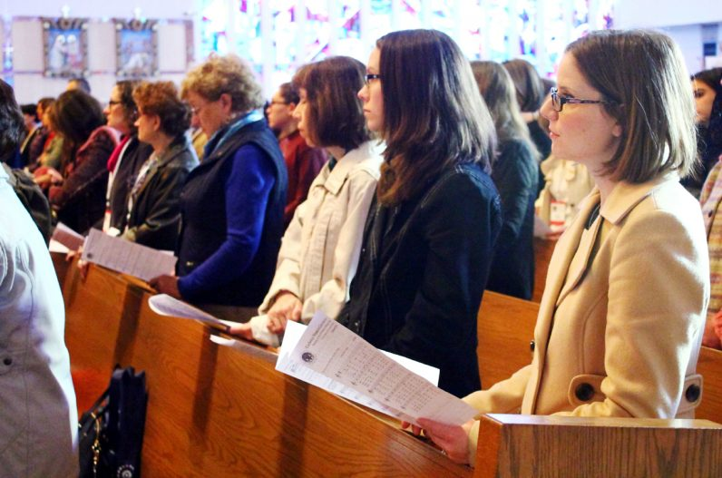 Danielle Gallagher, right, from St. Pius X Parish in Broomall prays with a full church at the National Shrine of Our Lady of Czestowchowa in Doylestown for the Catholic Women's Conference.