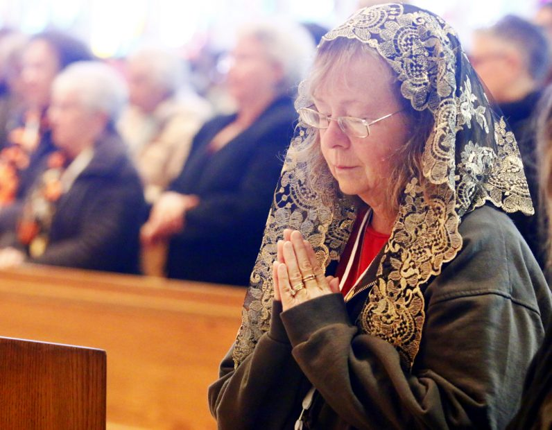 Robin Carosslli from St. Pius X Parish in Broomall prays during Mass.