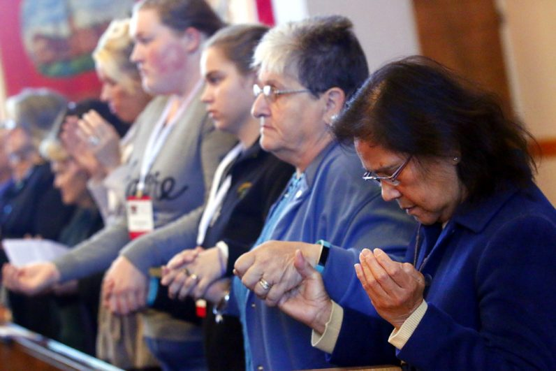 Divina Dayawon (right) from Our Lady of Consolation Parish in Parkesburg holds hands with other women while praying during the opening Mass of the conference.
