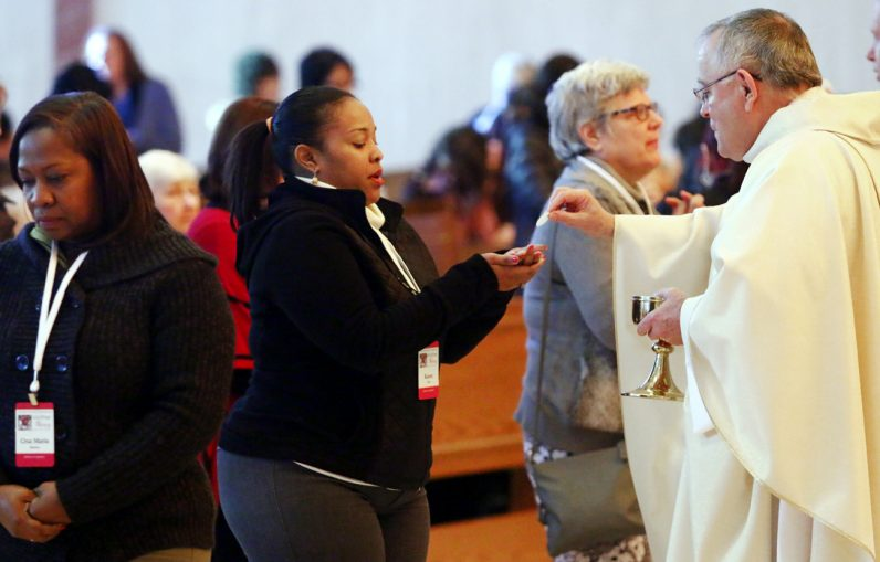 Archbishop Charles Chaput distributes Communion during Mass at the Catholic Women's conference Oct. 29 at the National Shrine of Our Lady of Czestochowa, Doylestown. (Sarah Webb)