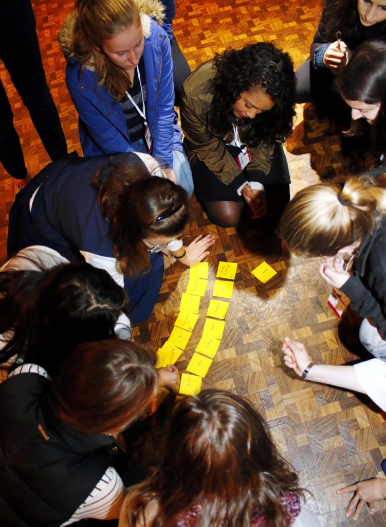 Women in the youth track work on an ice breaker where each were given a note with a word so they could come together to read a line of Scripture.