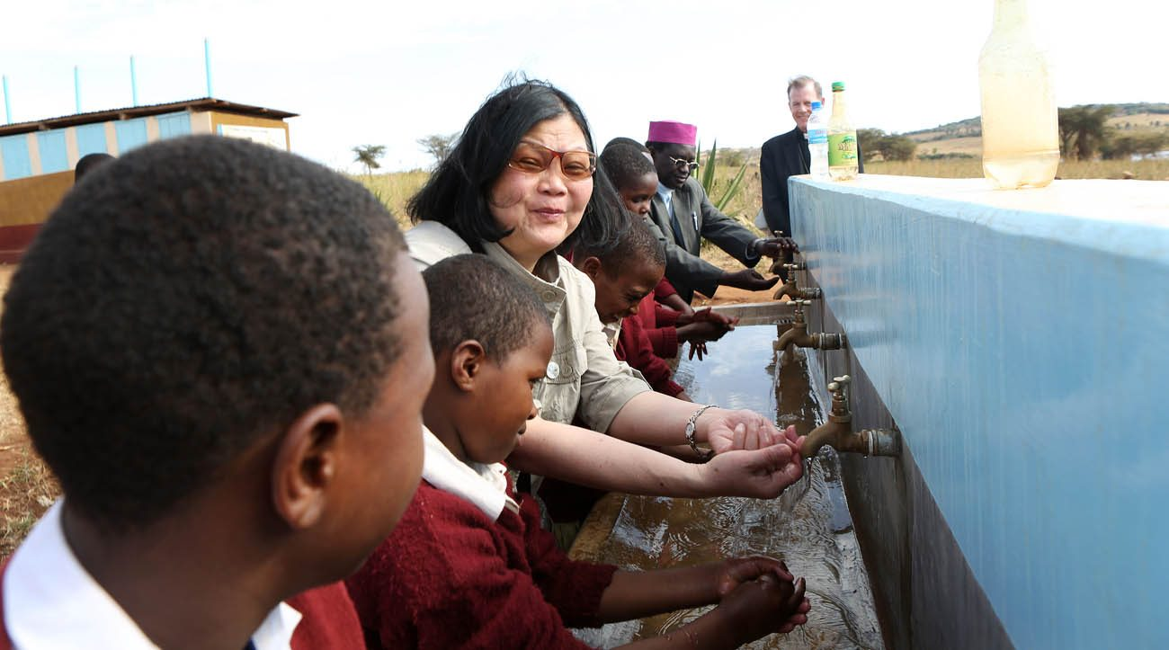 Carolyn Woo, outgoing CEO of Catholic Relief Services, washes her hands with Qaru Lambo primary school students in Karatu, Tanzania. She visited the area Oct. 3, 2013, as CRS celebrated 50 years of work in the country. Woo will end her five-year term as CEO of CRS at the end of 2016. (CNS photo/Sara A. Fajardo, courtesy Catholic Relief Services)