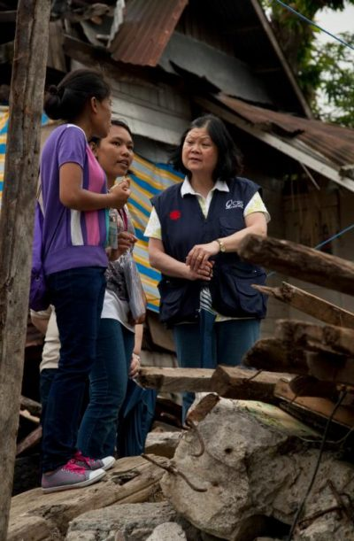 Carolyn Woo, outgoing CEO of Catholic Relief Services, talks with women about Typhoon Haiyan during a February 2014 visit to Tacloban, Philippines, three months after the typhoon devastated the nation. (CNS photo/Laura Elizabeth Pohl, courtesy Catholic Relief Services)