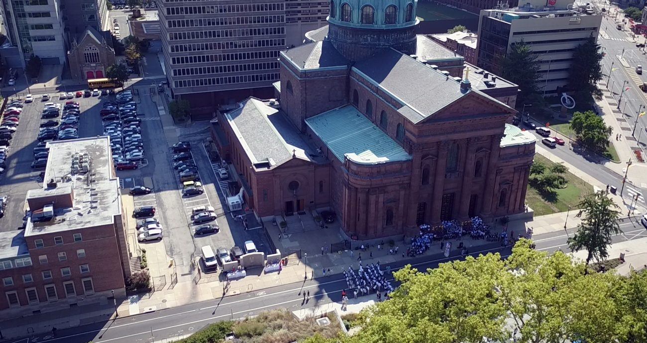 An aerial photo from September 2016 shows the Philadelphia block between Race (far right) and Vine Streets and 17th and 18th (bottom) Streets on which are sited the Cathedral Basilica of SS. Peter and Paul, the Holy Family Center (left) and Archdiocesan Pastoral Center (center rear), plus a rectory and convent. (Photo by Steve Newbert)