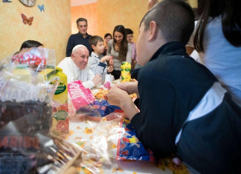 Pope Francis talks with young people during an Oct. 14 visit to Rome's SOS Children's Village. The village, which includes five houses, attempts to provide a home-like atmosphere for children under the age of 12 whose parents cannot care for them. (CNS photo/L'Osservatore Romano)
