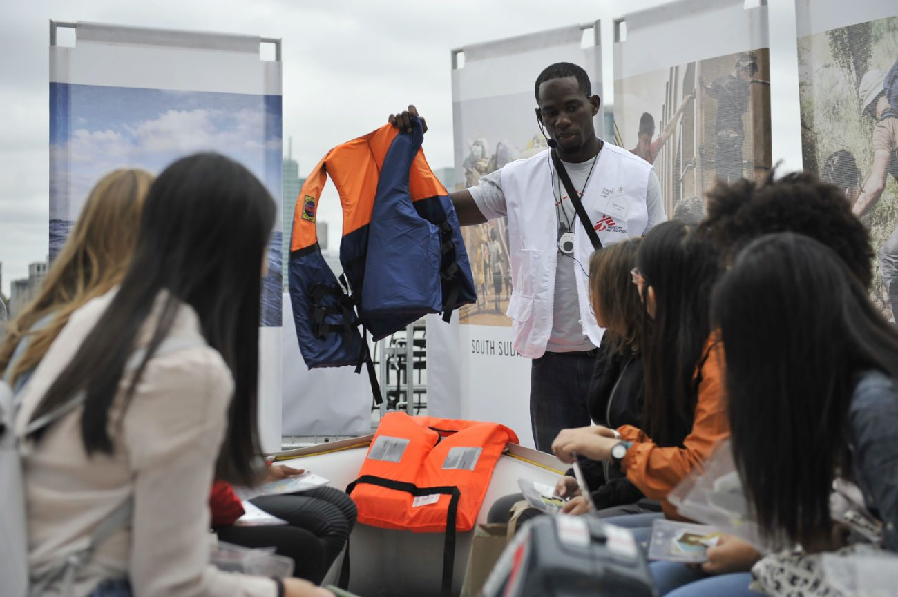 "A volunteer at the ""Forced from Home"" exhibit in Battery Park City, N.Y., holds up a life jacket Sept. 24 that doesn't work, pointing out that these are often sold to refugees fleeing their homeland by raft. (CNS photo/Elias Williams)"