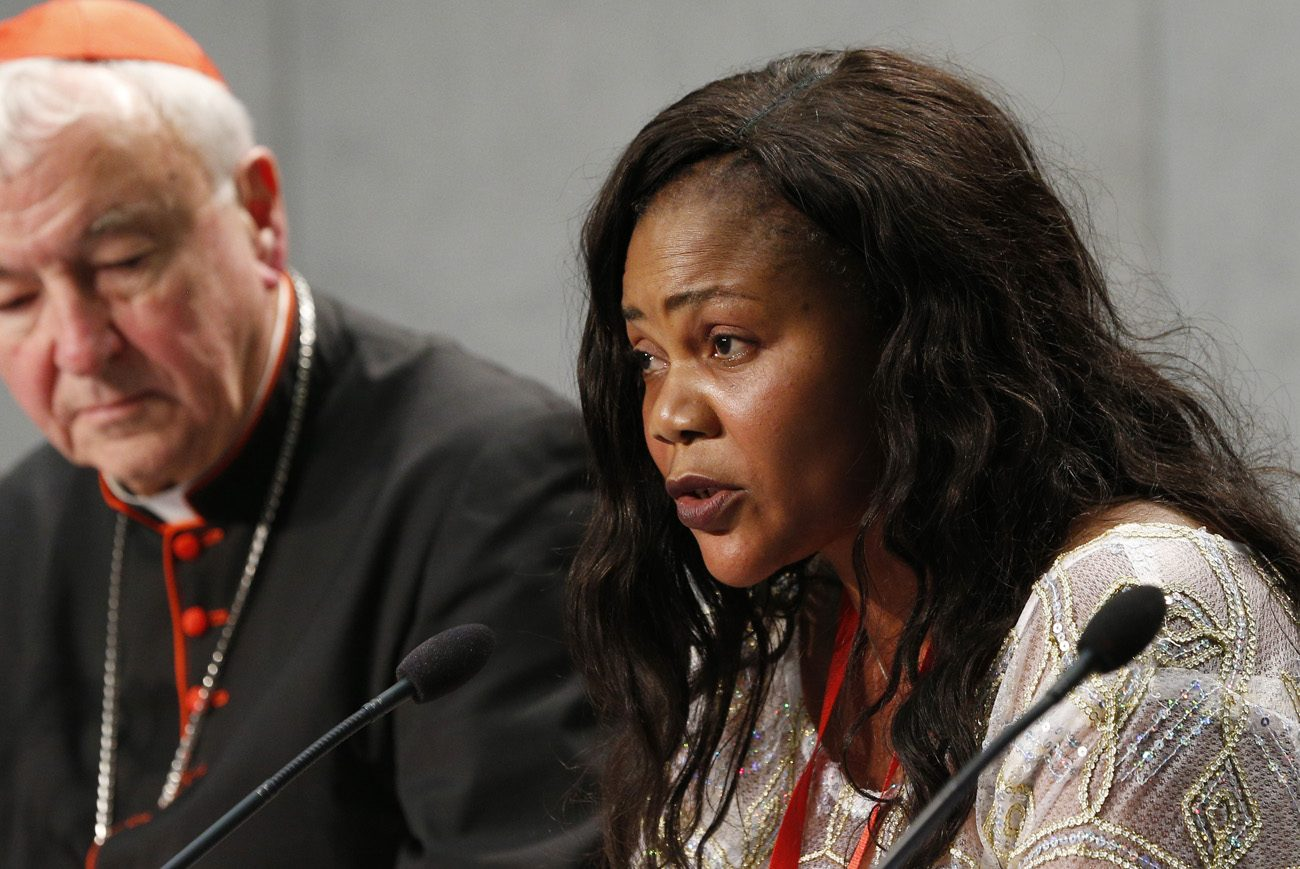 Princess Inyang, who was forced into prostitution by a human trafficker, speaks at a news conference at the Vatican Oct. 27. Also pictured is Cardinal Vincent Nichols of Westminster, England. Inyang and other trafficking survivors spoke at a conference on human trafficking organized by the Santa Marta Group at the Vatican. The group is an international coalition of senior law enforcement chiefs and Catholic bishops. (CNS photo/Paul Haring)