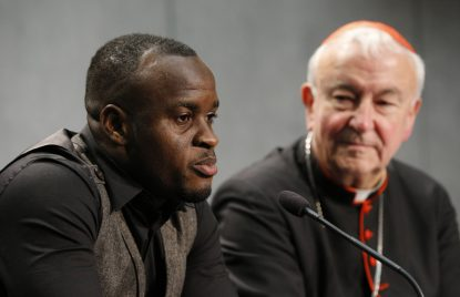 Al Bangura, who was forced into sexual slavery by a human trafficker, speaks at a news conference at the Vatican Oct. 27. Also pictured is Cardinal Vincent Nichols of Westminster, England. (CNS photo/Paul Haring)