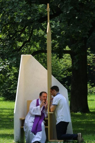 """A priest hears confession from a World Youth Day pilgrim at Park Jordana in Krakow, Poland, July 26. When Pope Francis launched his missionaries of mercy on Ash Wednesday, he reminded them, """"Let us not forget: Before us is not a sin, but a contrite sinner."""" (CNS photo/Bob Roller)"""