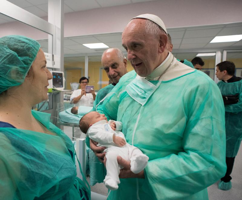 Pope Francis holds a baby as he visits the neonatal unit at San Giovanni Hospital in Rome Sept. 16, a visit that was part of the pope's series of Friday works of mercy during the Year of Mercy. The Year of Mercy was declared to help us to understand just how essential God's mercy is to the Christian faith, and how living a life of mercy is essential to living that faith. (CNS photo/L'Osservatore Romano)