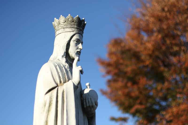 A statue depicting the kingship of Jesus is seen by a tree that is about to lose its leaves for the winter at Christ the King Church in Commack, N.Y., just before the start of Advent 2015. (CNS photo/Gregory A. Shemitz)