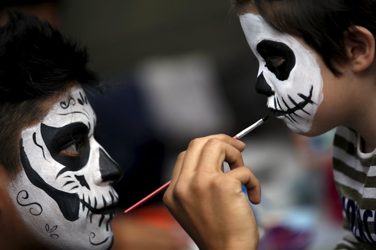 "A man paints a boy's face to look like ""Catrina"" in Mexico City, as part of Day of the Dead celebrations Nov. 1. In Mexico ""Catrina"" symbolizes elegant death. (CNS photo/Carlos Jasso, Reuters)"