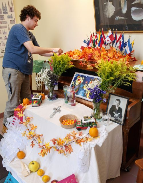 Ryan Pallas, a Spanish-language student at Nazareth College, helps decorate a Day of the Dead altar at the college in Pittsford, N.Y., Nov. 2. The Mexican tradition is often observed by families who build altars in their homes and decorate them with flowers, food and sugar skulls in honor of deceased loved ones. (CNS photo/Mike Crupi, Catholic Courier)