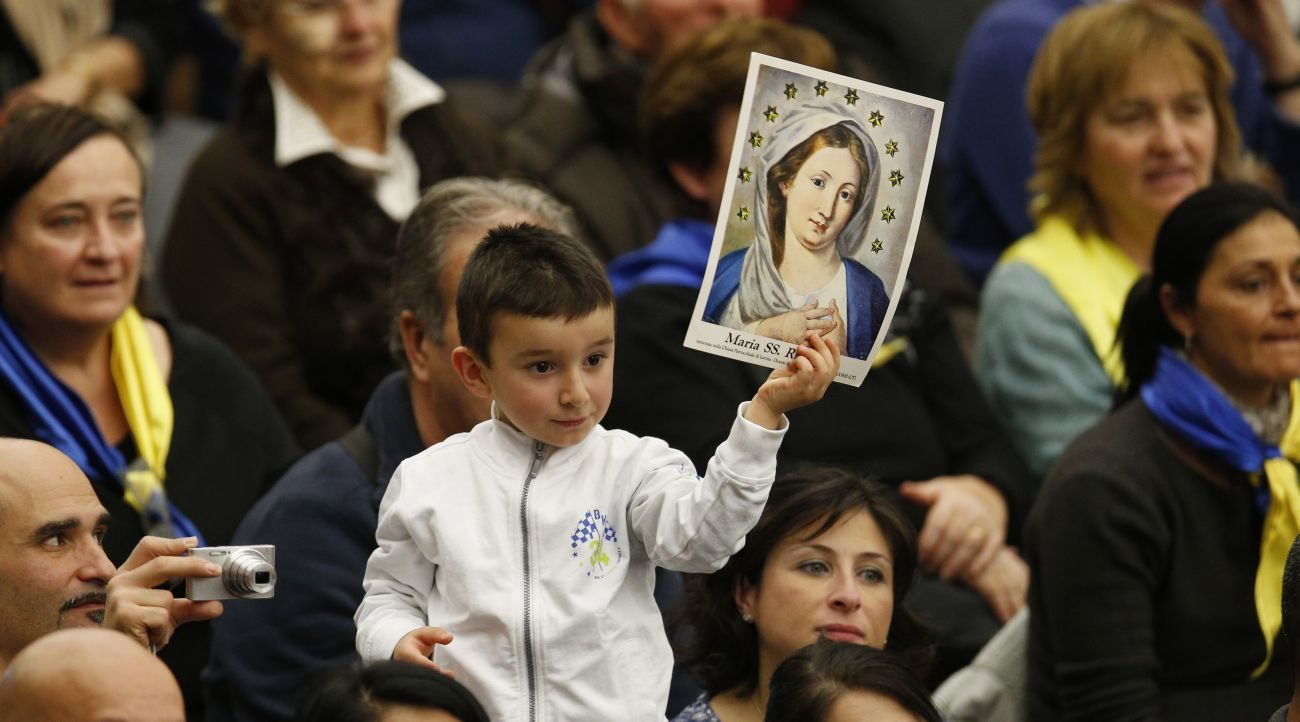 A boy holds an image of Mary as Pope Francis leads his general audience in Paul VI hall at the Vatican Nov. 30. (CNS photo/Paul Haring)