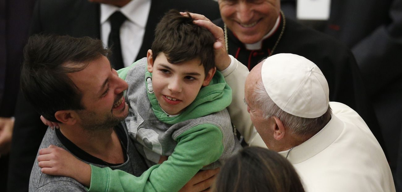 Pope Francis greets a boy while meeting the disabled during his general audience in Paul VI hall at the Vatican Nov. 30. (CNS photo/Paul Haring)