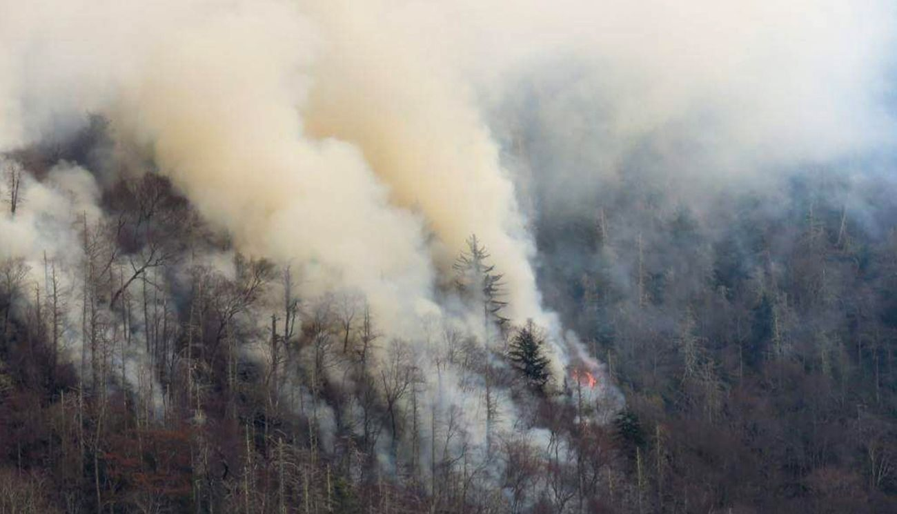 Smoke plumes from wildfires are seen Nov. 29 along the Smoky Mountains National Park near Gatlinburg, Tenn. Raging wildfires fueled by high winds claimed the lives of at least three people, forced the evacuation of thousands, including Father Antony Punnackal of St. Mary's Church, and damaged hundreds of buildings in the popular mountain resort town. (CNS photo/courtesy National Park Services handout via Reuters)