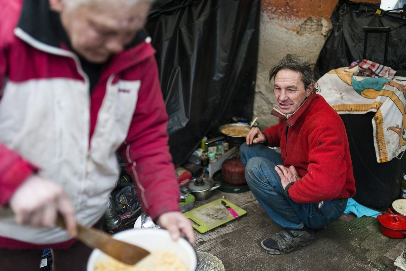 "A homeless couple cooks a meal outside their makeshift shelter in late January in Budapest, Hungary. Europe's top Catholic charitable agency has published a ""road map for social justice and equality,"" urging all church members to defend the poor and marginalized. (CNS photo/Attlia Balazs, EPA)"