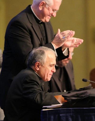 Archbishop Joseph E. Kurtz of Louisville, Ky., outgoing president of the U.S. Conference of Catholic Bishops, applauds Nov. 15 after Cardinal Daniel N. DiNardo of Galveston-Houston, seated, was elected president during the annual fall general assembly of the USCCB in Baltimore. (CNS photo/Bob Roller)