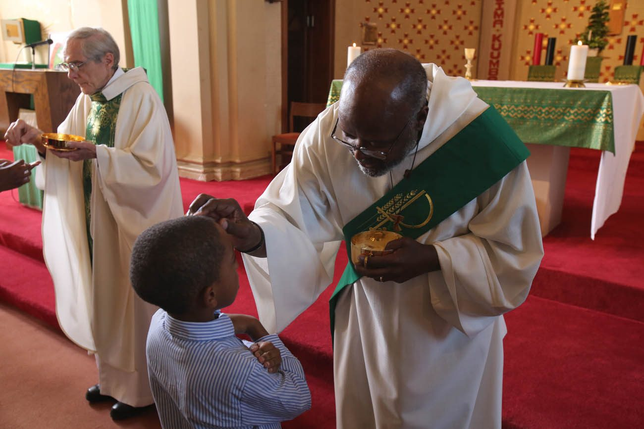 Deacon Willard Witherspoon blesses a boy during Mass Nov. 13 at St. Peter Claver Church in Baltimore. The U.S. bishops will concelebrate Mass at the church Nov. 14, the first day of their fall general assembly. (CNS photo/Bob Roller)