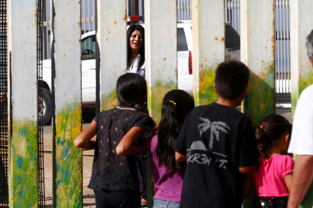 A woman in San Diego talks through a fence with children in Tijuana, Mexico, Nov. 12. (CNS photo/Jorge Duenes, Reuters)