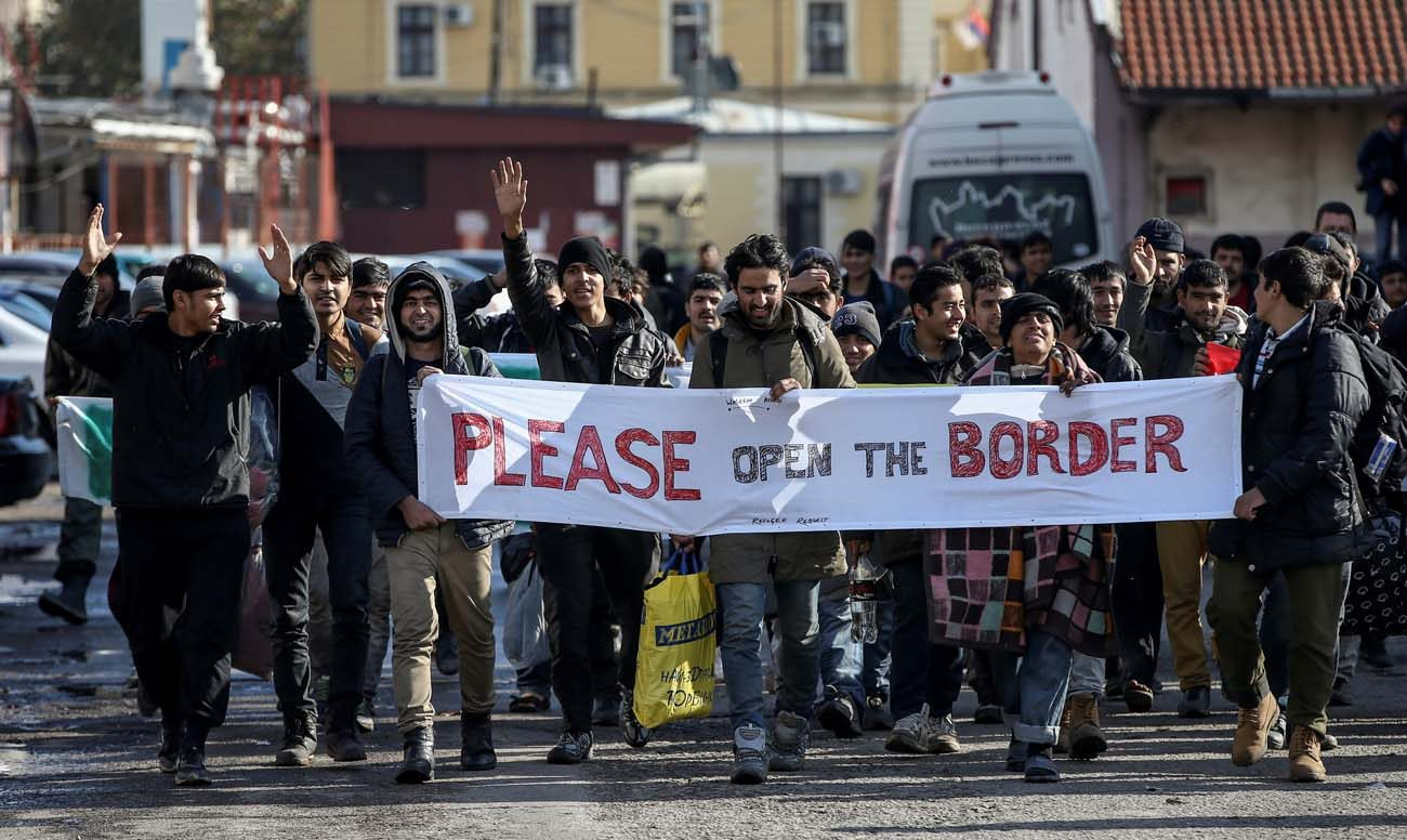 Refugees and migrants hold a banner and shout slogans Nov. 11 as they walk toward the Croatian border in Belgrade, Serbia. English Cardinal Vincent Nichols said some British media stirred up xenophobic sentiments against migrants and refugees. (CNS photo/Marko Djurica, Reuters)