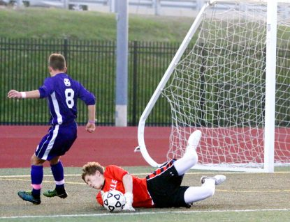 Brett Werner in red) makes a big save during a game in which he gave up only one goal en route to the Explorers championship victory over Roman Catholic Sarah Webb)
