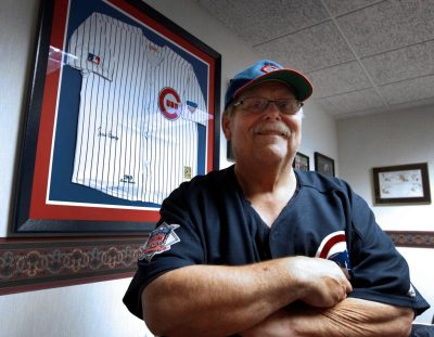 Father John W. Clemens, pastor of Our Lady of Hope Church in Rosemont, Ill., poses for a photo Oct. 27 near his jersey signed by Chicago Cubs legend Ernie Banks. (Karen Callaway/Catholic New World)