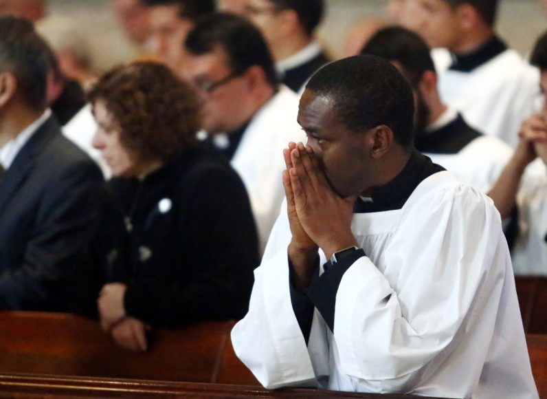 Kevin C. Okafor prays during Mass where he was admitted to candidacy at St Charles Borromeo Seminary.