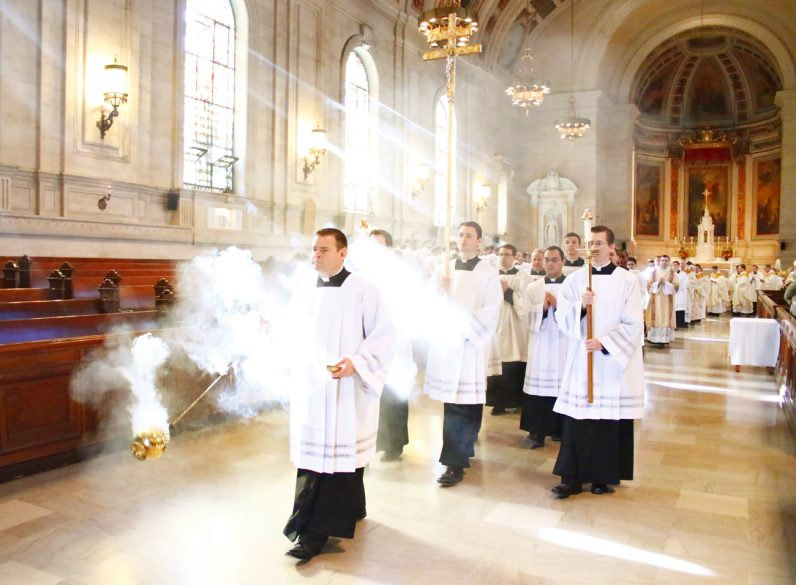 Seminarian John Howarth bathes a light-flooded St. Martin's Chapel in fragrant smoke as he leads the recessional at the end of Mass on the feast of St. Charles Borromeo.