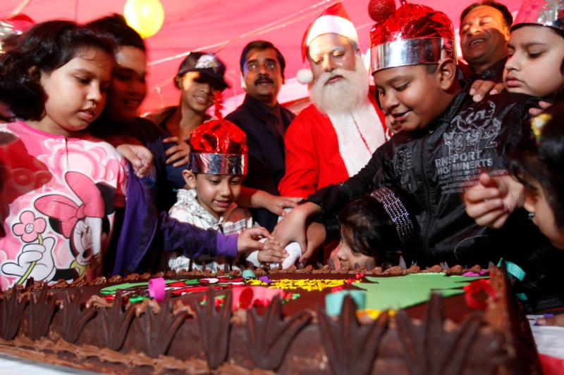 A man dressed as Santa Claus cuts a cake along with children during a 2012 Christmas celebration in a hotel in Dhaka, Bangladesh. A Christmas tradition, like a Christmas cake, holds tremendous power, because it helps the participants feel secure and strengthens their spiritual ties to faith and one another. (CNS photo/Abir Abdullah, EPA)