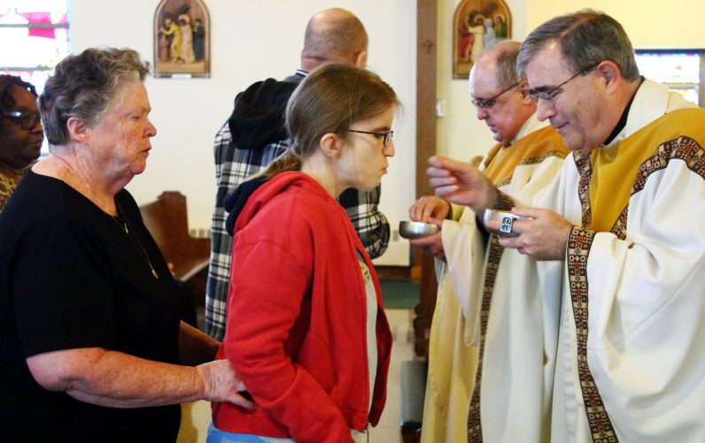 Father Francis Mulranen, pastor of Our Lady of Fatima Parish in Secane where Our Lady of Fatima Center is located, distributes holy Communion to a client assisted by Sister. Mary Veasey, S.S.J.