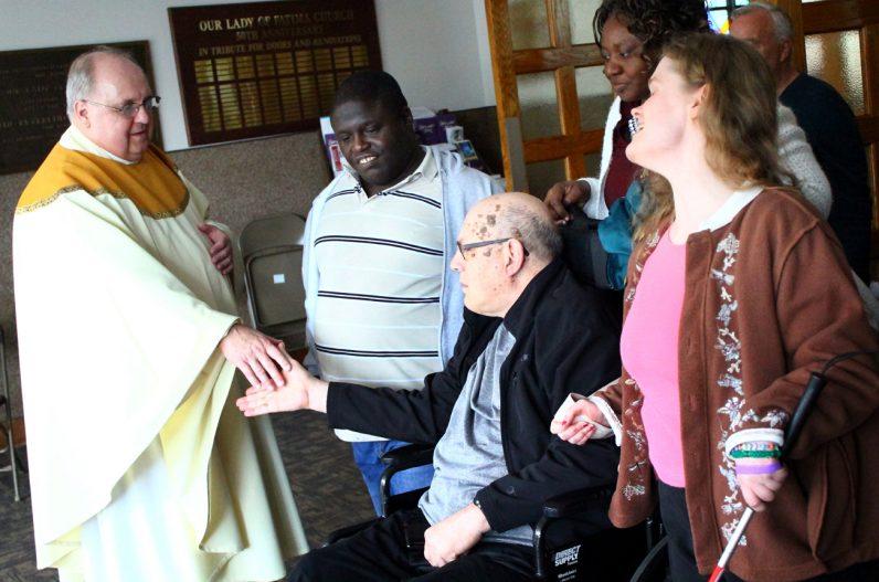 Father Dennis Weber, S.d.C, greets participants after Mass.
