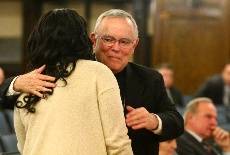 Archbishop Charles Chaput embraces Jasmine Mays, a West Catholic graduate and now a freshman at Villanova University.