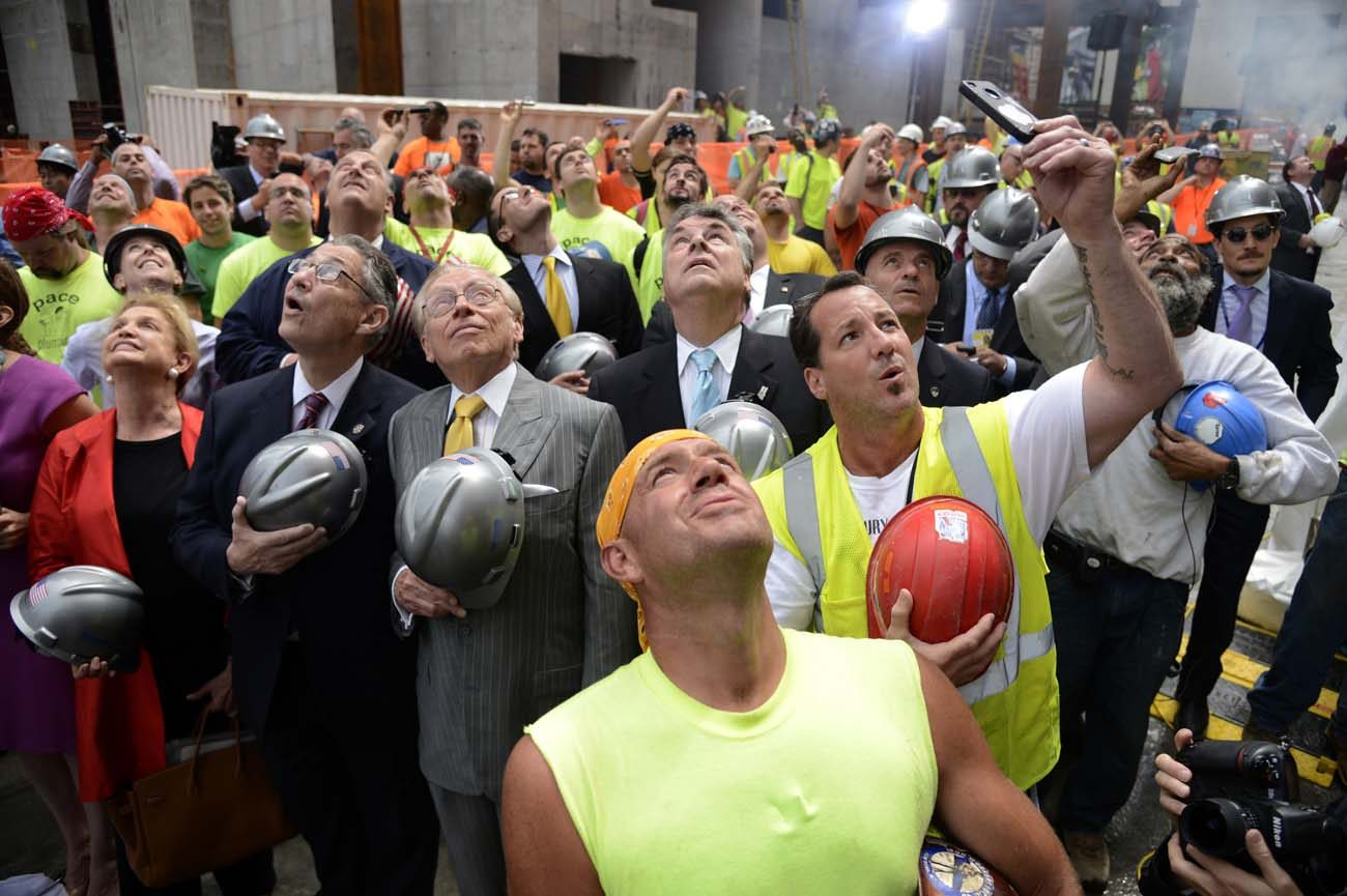 Developers and construction workers watch the final steel beam lifted to the top of 4 World Trade Center in New York City in this 2012 photo. President-elect Donald J. Trump credits blue-collar workers for his unexpected rise to the presidency of the United States. (CNS photo/Andrew Gombert, EPA)